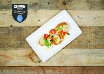 City College Norwich Starter - Mozzarella chilli and basil Arancini, with a sweet potato puree, garnished with a baked cherry tomatoes, and grilled baby