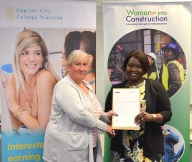 A graduate of the Women in Construction programme receives their completion certificate